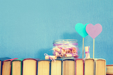 Valentines day concept. Dreams written on a pink rolled paper in a glass jar, blue paper heart, violet paper heart on books over blue background. Toned.