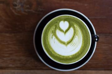 matcha green tea latte with heart shape latte art on wooden table