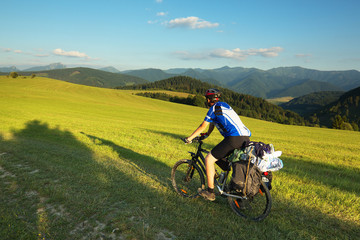 Tourist on bicycle with mountain on background, Slovakia