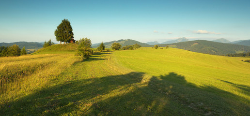Panoramic view of a meadow with a small chapel and mountains  in Slovakia