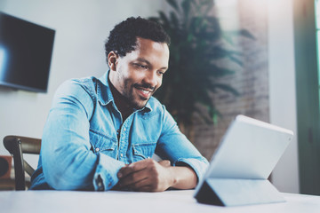 Smiling young African man making video conversation via digital tablet with friends while sitting at the table in modern office.Concept of happy business people.Blurred background, film effect.