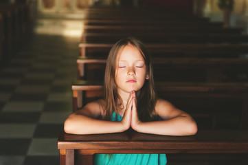 Child praying in church