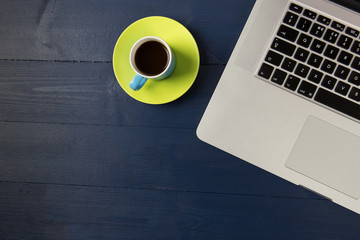 Coffee and laptop on blue wood desk