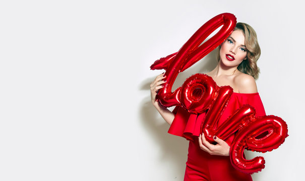Valentine's Day. Word love letters from the inflatable. Girl holding a big word love.Girl with retro hairstyle in red dress in red high heels in studio on a white background.