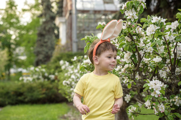 Little boy hunting for easter egg in spring garden on day. Cute