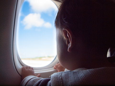 A baby looking out from an airplane window