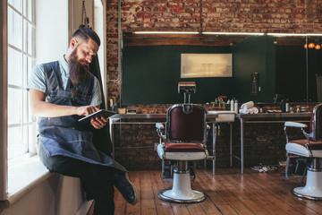 Barber organizing his business using digital tablet
