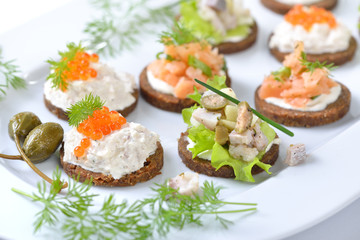 Leckeres Fisch-Fingerfood mit Lachstatar, Matjestatar und Forellencreme mit Kaviar -  Finger food with salmon tartar, trout mousse with caviar and herring salad on pumpernickel bread