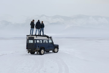 Three male friends standing on the roof of old 4x4 off-road vehicle, enjoying the view of mountains over large lake. 4K UHD 60 FPS RAW edited footage