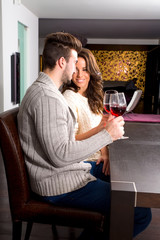Young couple having a romantic evening with a glass of wine.