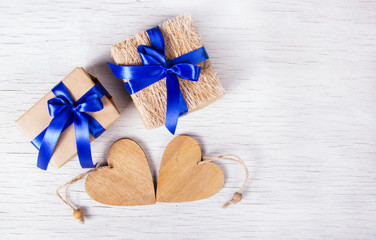 Two gift boxes with blue ribbons and wooden hearts on a white background. Valentine's Day. Copy space.