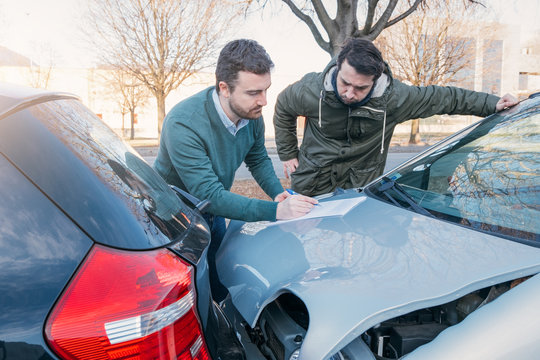 Two men writing a car insurance claim after a car crash