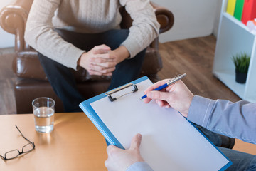 Psychologist taking notes during psychotherapy session