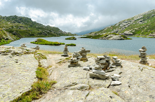 Rock piles on slab in the Swiss Alps with a mountain lake behind that extends to the horizon. A Swiss flag is seen on a little island in the middle of the lake