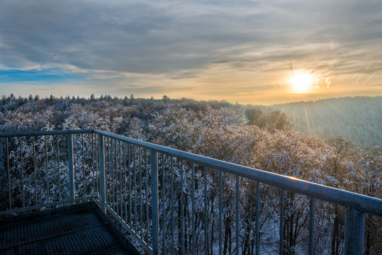 Beautiful sunset viewed over snow covered trees that extend to the horizon. The sun in its orange color is shining trough the cloud cover hitting the trees and railing in the foreground.
