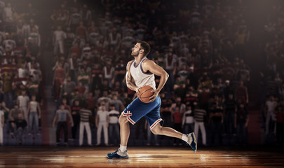 basketball player on parquet with ball in light rays