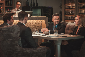 Group of successful business people discussing during business dinner in restaurant