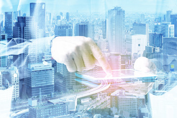 Double exposure of businessman hand touching digital tablet over