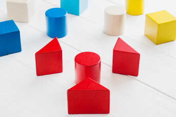 Colorful wooden blocks on white wooden background. Creativity toys. Children's building blocks. Geometric shapes - cube, triangular prism, cylinder. The concept of logical thinking.