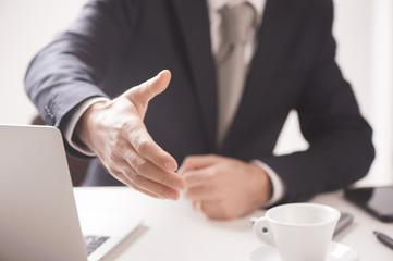 Close up of businessman's hand offering handshake