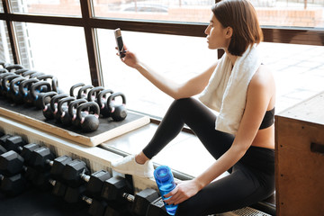 Sportswoman taking selfie with cell phone in gym