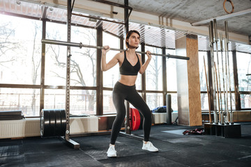 Sportswoman standing and working out in gym