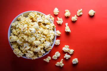 popcorn in white bowl on the red background