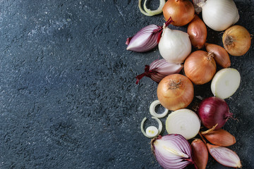 Variety of whole and sliced red, white, yellow and shallot onions over dark stone texture background. Top view, space for text