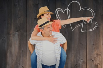 Composite image of happy man piggy backing wife