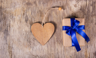 Gift box with blue bow and Valentine. Surprise on Valentine's Day. Wooden heart. Copy space. Valentine's day.