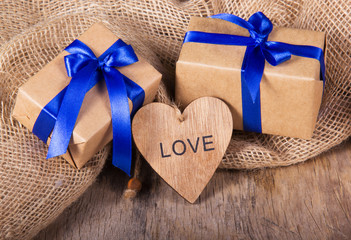 Gift boxes from recycled paper decorated with blue satin bow. Wooden Valentine on the old wooden background. Valentine's Day.