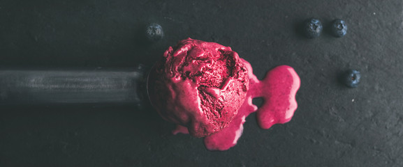 Melting scoop of blueberry ice-cream over black slate stone background, top view, selective focus