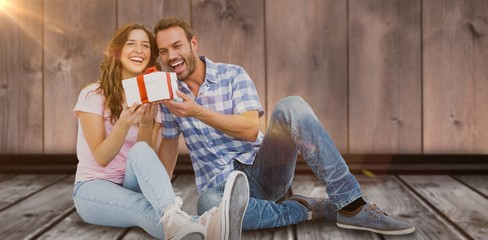 Composite image of happy young couple holding gift