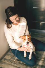 Young and beautiful smiling woman sitting with her pet dog on the floor at home