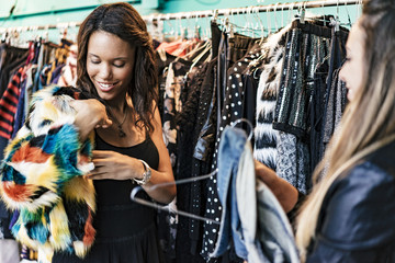 two female mixed race friends buying clothes in a store