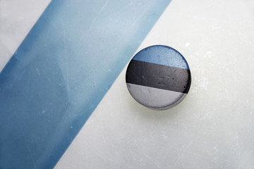 old hockey puck with the national flag of estonia.