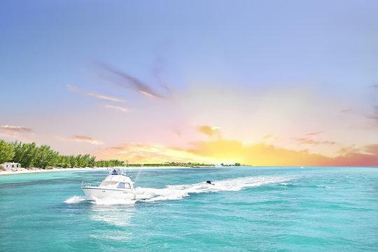 White boat sails the sea from the sundown horizon