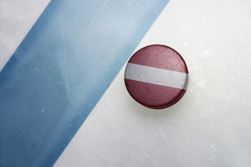 old hockey puck with the national flag of latvia.