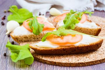 Сандвичи из ржаного хлеба с плавленным сыром, помидором и рукколой