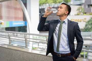 businessman standing drink water in area building when work hard