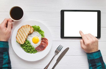 Healthy morning breakfast online browsing concept with tablet blank pure white screen for text or picture design. Man's hands with eggs, peas, bread and juice meal. Modern people lifestyle flat lay