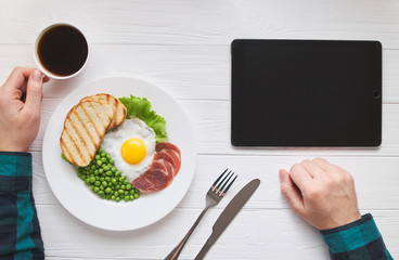 Healthy morning breakfast concept with tablet device blank screen for text or picture design. Man's hands with eggs, peas, bread and juice lunch or brunch meal. Modern people lifestyle flat lay