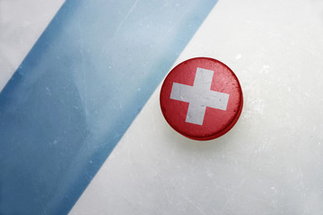 old hockey puck with the national flag of switzerland.