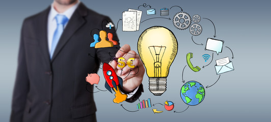 Businessman drawing a lightbulb with a pen with multimedia icons