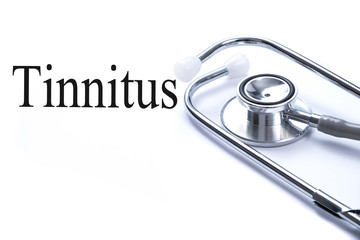 Page with Tinnitus on the table with stethoscope, medical concep