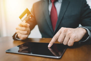 Businessman hand using tablet and credit card for online shopping or banking. Fintech concept.