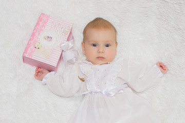 little girl in white dress, after the baptism of a Christian cross, lying on his back on a white fur rug of a beautiful box, white background, three months