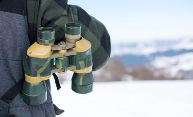 Man with binoculars exploring snowy mountain
