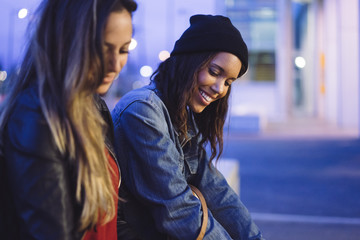two young female friends chatting and looking at smartphone