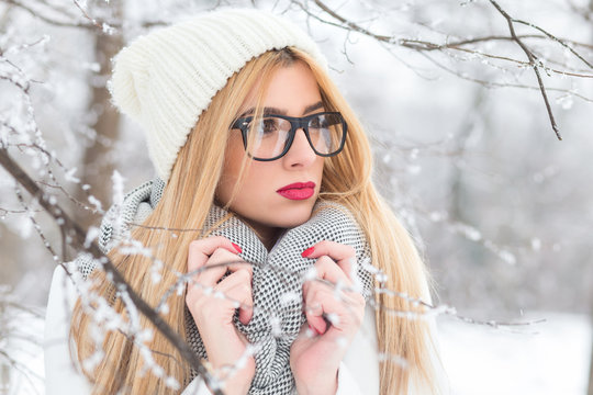 Winter portrait of beautiful blonde woman with glasses in park.